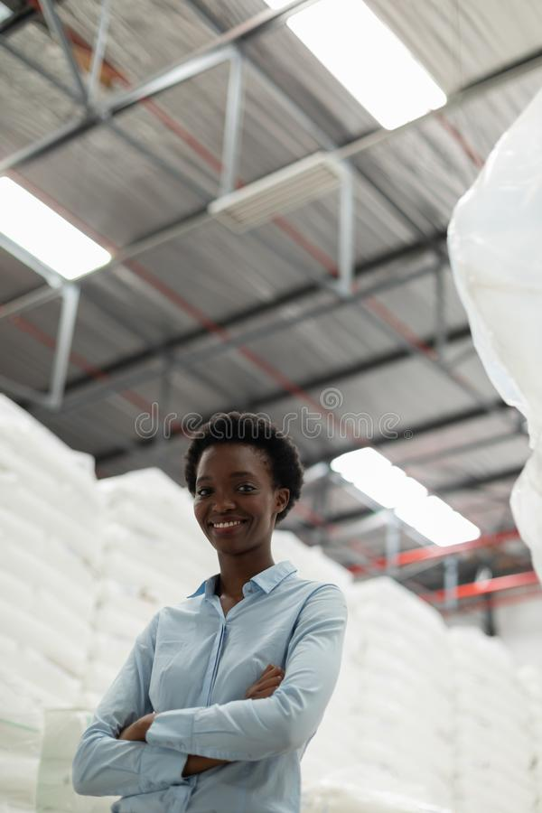 Female manager with arms crossed looking at camera in warehouse. Low angle view of female manager with arms crossed looking at camera in warehouse. This is a stock images