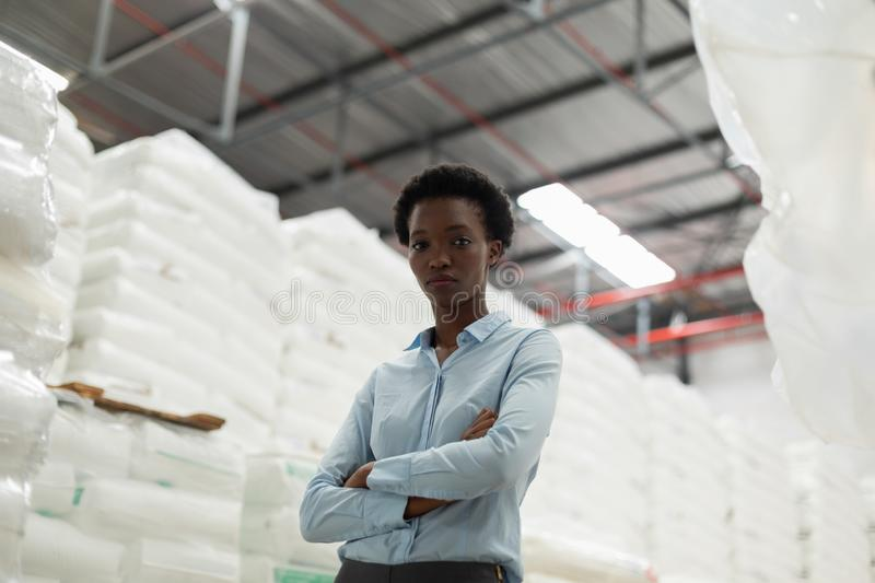 Female manager with arms crossed looking at camera in warehouse. Low angle view of female manager with arms crossed looking at camera in warehouse. This is a royalty free stock photo