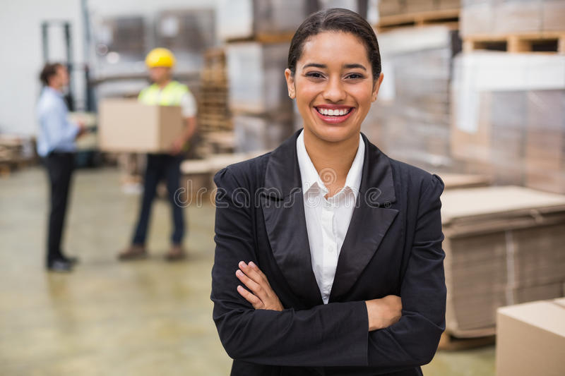 Female manager with arms crossed in warehouse stock photography