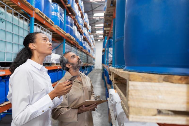 Female manager checking inventory in warehouse. Side view of female manager checking inventory in warehouse. This is a freight transportation and distribution stock photography