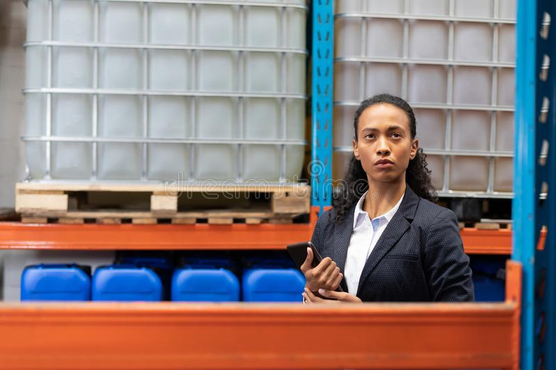 Female manager checking stocks while using digital tablet in warehouse. African American female manager checking stocks while using digital tablet in warehouse stock photo