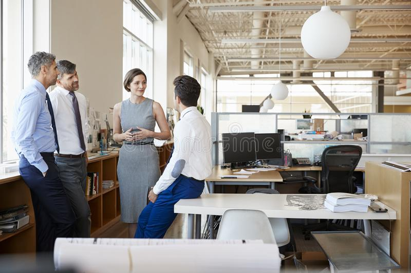 Female manager and colleagues talking in an open plan office stock photo