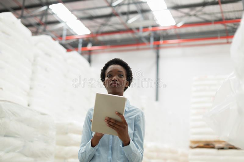 Female manager with digital tablet checking stocks in warehouse. Front view of female manager with digital tablet checking stocks in warehouse. This is a freight stock image
