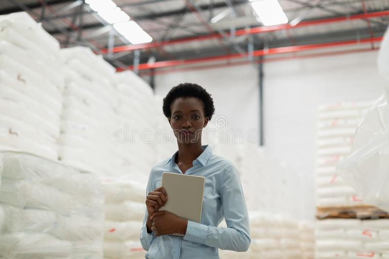 Female manager with digital tablet looking at camera in warehouse. Front view of female manager with digital tablet looking at camera in warehouse. This is a stock images