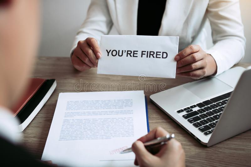 Female manager handed out the dismissal certificate to the male employee while signing the contract to quit from or resign.  royalty free stock photography
