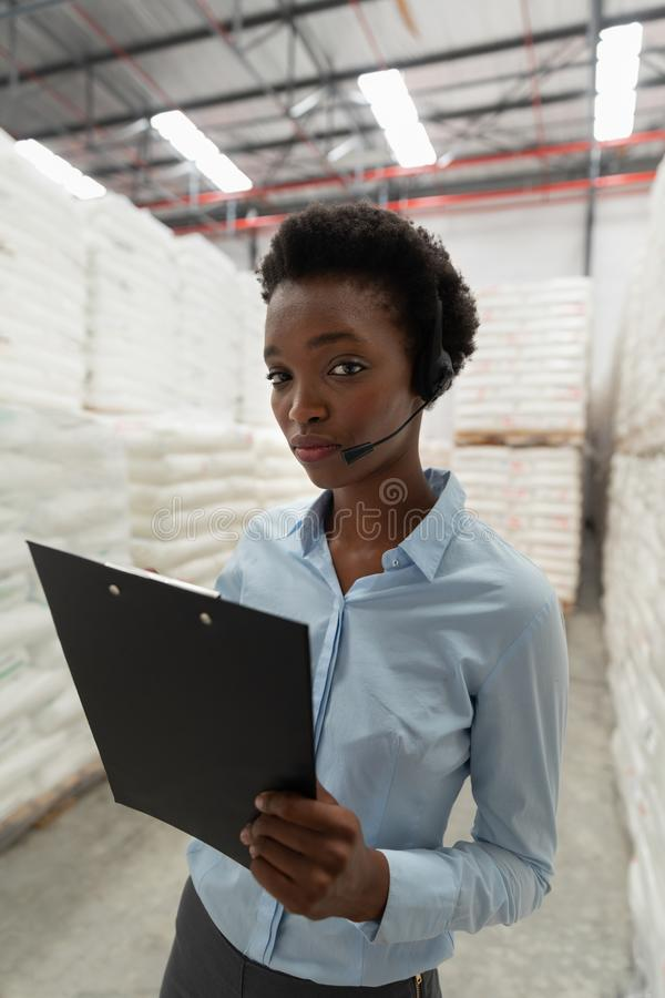 Female manager with headset and clipboard looking at camera in warehouse. Close-up of female manager with headset and clipboard looking at camera in warehouse royalty free stock photos