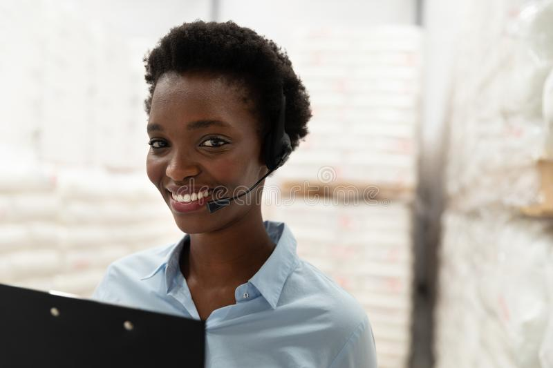 Female manager with headset and clipboard looking at camera in warehouse. Close-up of female manager with headset and clipboard looking at camera in warehouse royalty free stock photography