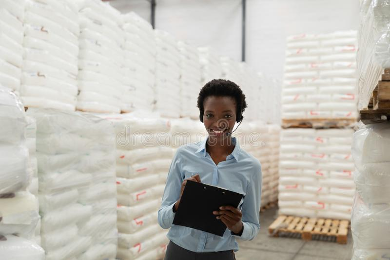 Female manager with headset writing on clipboard in warehouse. Portrait of female manager with headset writing on clipboard in warehouse. This is a freight stock photo