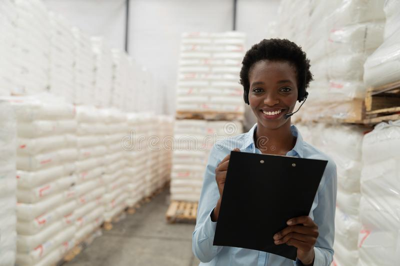 Female manager with headset writing on clipboard in warehouse. Portrait of female manager with headset writing on clipboard in warehouse. This is a freight royalty free stock photo