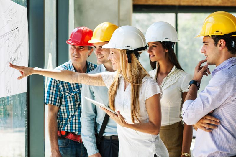 Female manager and her architects and experts discuss about construction project. Female manager and her architects and experts discuss about construction stock photo