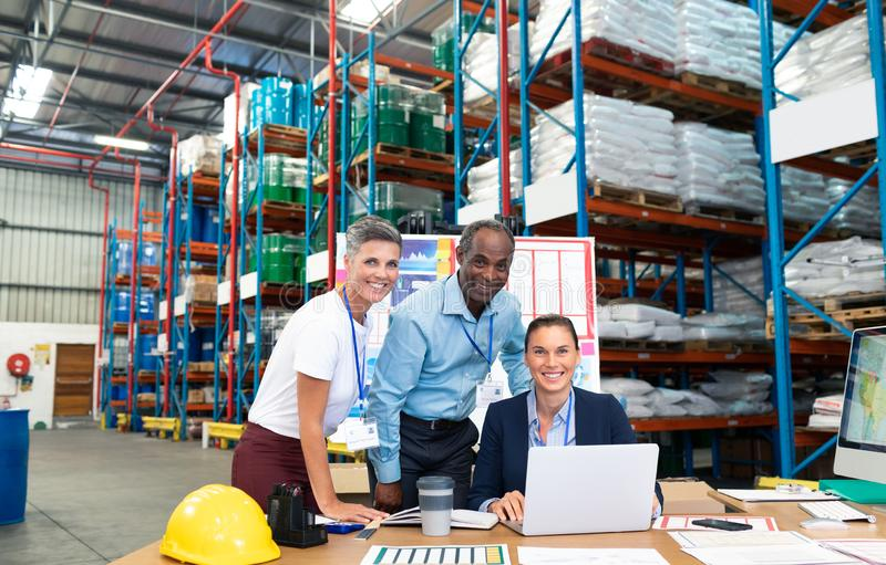 Female manager with her coworkers discussing over laptop at desk in warehouse. Portrait of beautiful Caucasian female manager with her coworkers discussing over royalty free stock photo