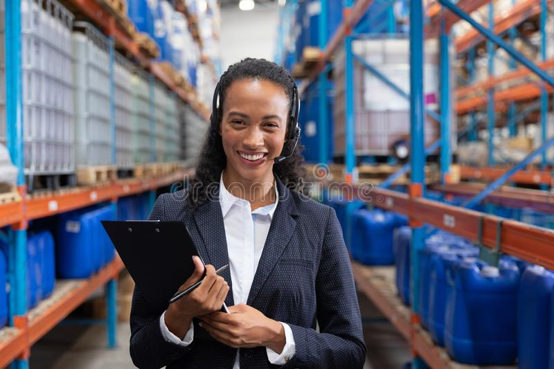 Female manager looking at camera while holding clipboard in warehouse. Happy female manager looking at camera while holding clipboard in warehouse. This is a royalty free stock photo