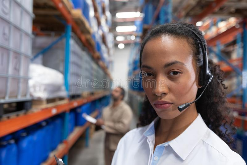 Female manager looking at camera while standing in warehouse. Close-up of female manager looking at camera while standing in warehouse. This is a freight royalty free stock photography