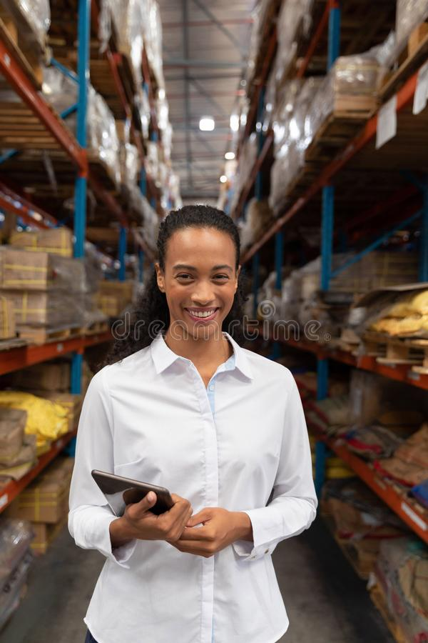 Female manager looking at camera while standing in warehouse. Happy female manager looking at camera while standing in warehouse. This is a freight royalty free stock photography