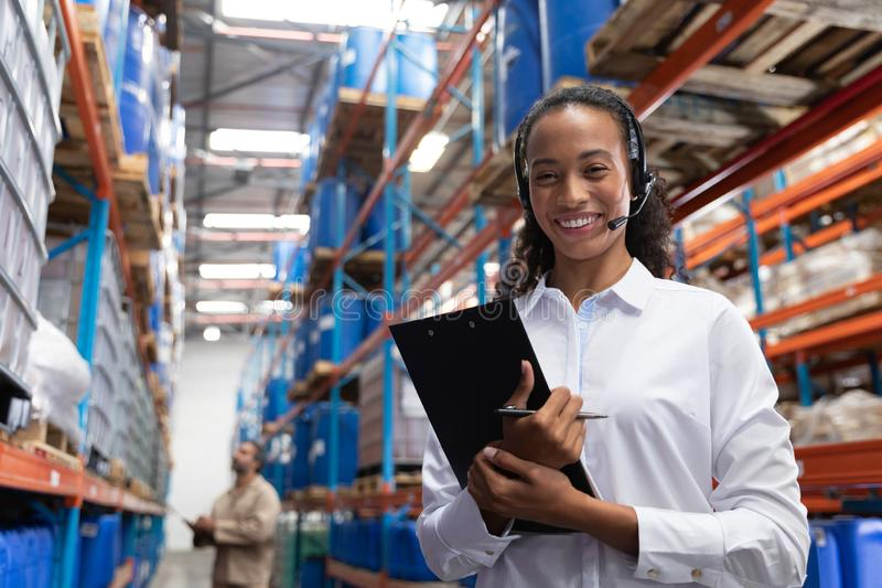 Female manager looking at camera while standing in warehouse. Portrait of female manager looking at camera while standing in warehouse. This is a freight stock image