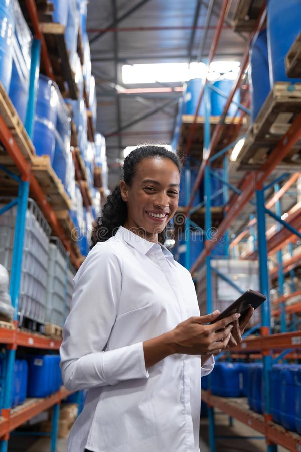 Female manager looking at camera while using digital tablet in warehouse. Portrait of female manager looking at camera while using digital tablet in warehouse royalty free stock images
