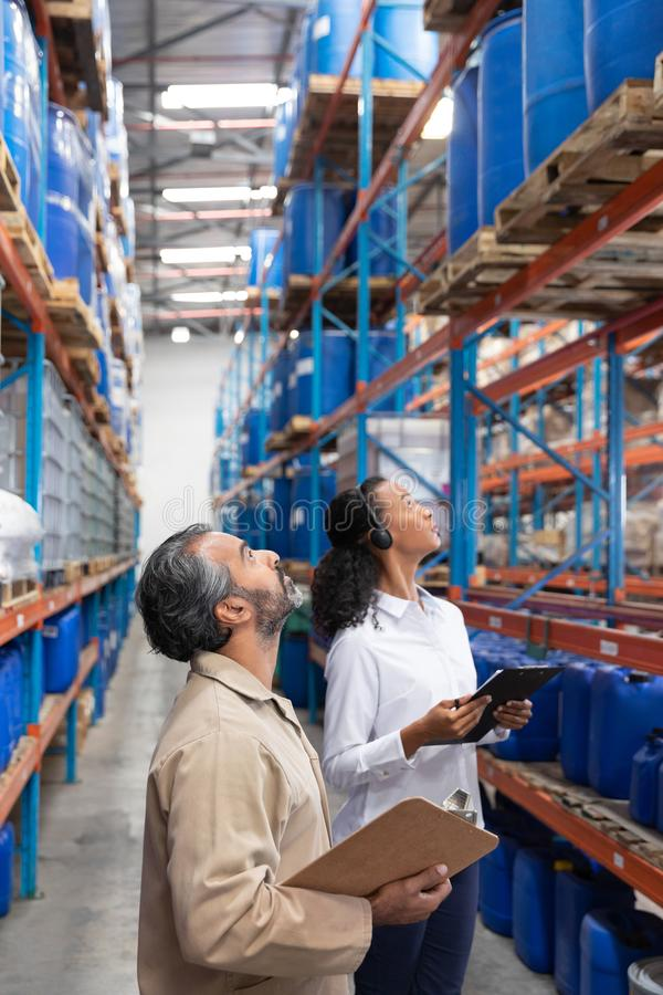 Female manager and male staff checking stocks in warehouse. Female manager and male staff checking stocks together in warehouse. This is a freight transportation stock image