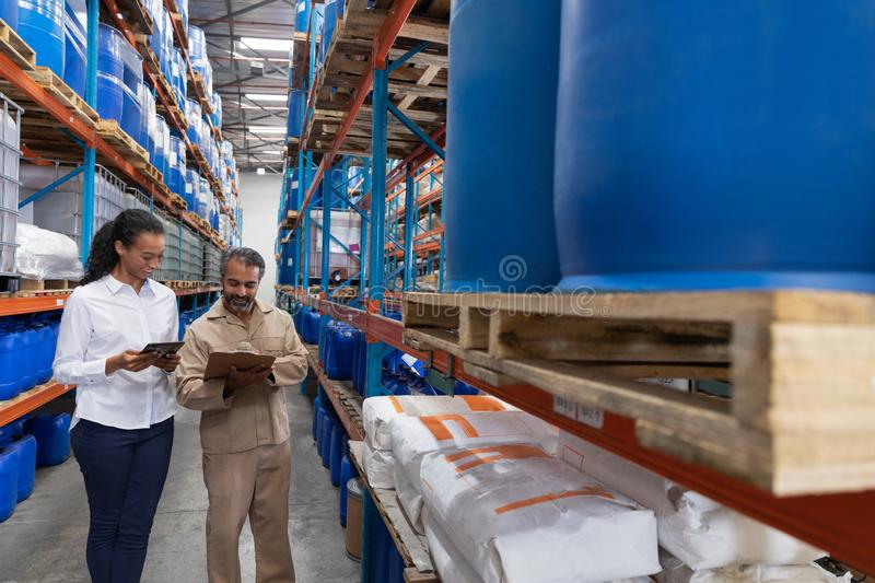 Female manager and male staff discussing over clipboard in warehouse. Front view of female manager and male staff discussing over clipboard in warehouse. This is stock photos