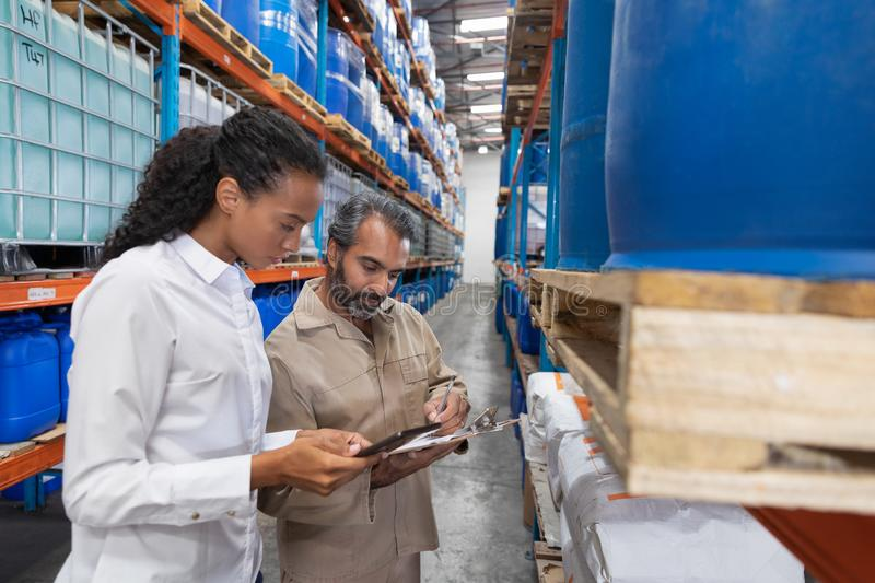 Female manager and male staff discussing over clipboard in warehouse. Side view of female manager and male staff discussing over clipboard in warehouse. This is royalty free stock images