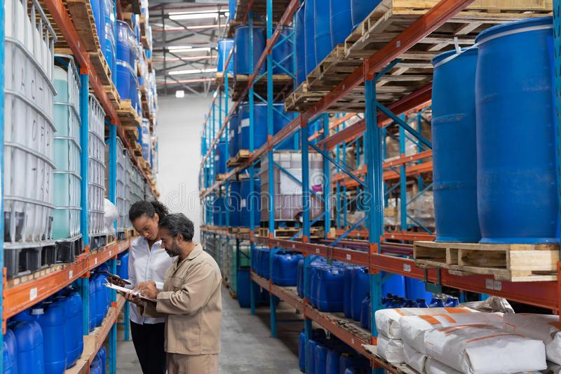 Female manager and male staff discussing over clipboard in warehouse. Side view of female manager and male staff discussing over clipboard in warehouse. This is royalty free stock photos