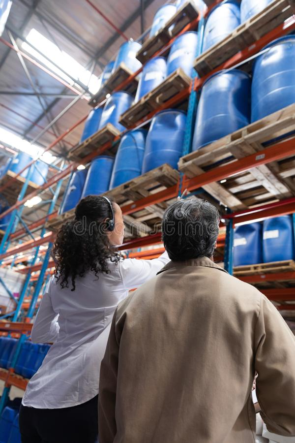 Female manager and male staff interacting with each other while checking stocks in warehouse. Low angle view of female manager and male staff interacting with stock images