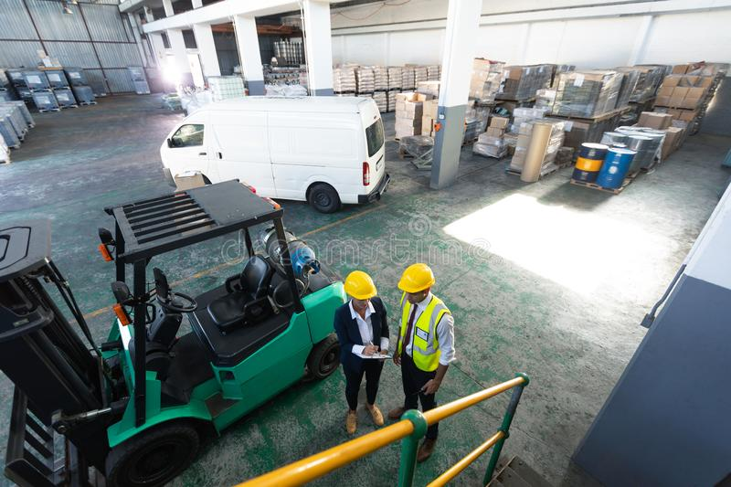 Female manager and male supervisor discussing over clipboard in warehouse. High angle view of Caucasian female manager and male supervisor discussing over royalty free stock photo