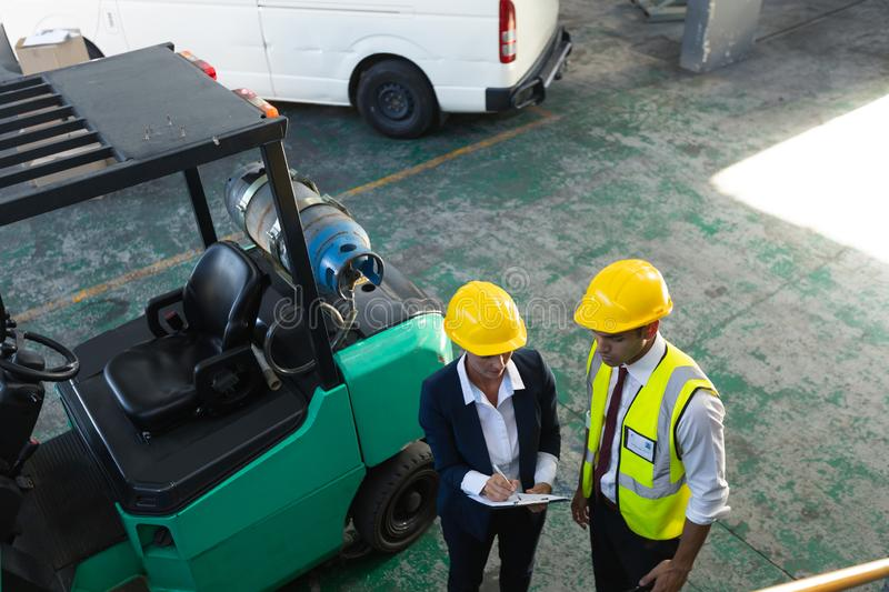 Female manager and male supervisor discussing over clipboard in warehouse. High angle view of Caucasian female manager and male supervisor discussing over royalty free stock photography