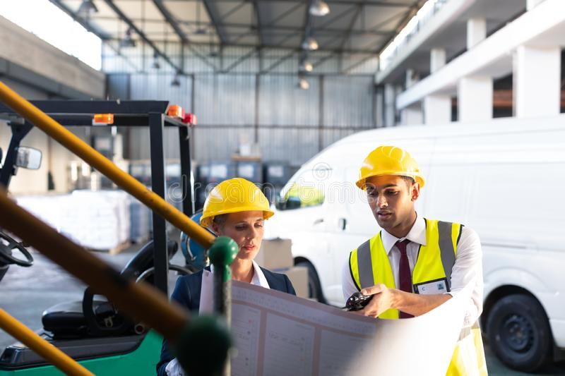 Female manager and male supervisor discussing over inventory chart in warehouse. Front view of Caucasian female manager and Caucasian male supervisor discussing royalty free stock image