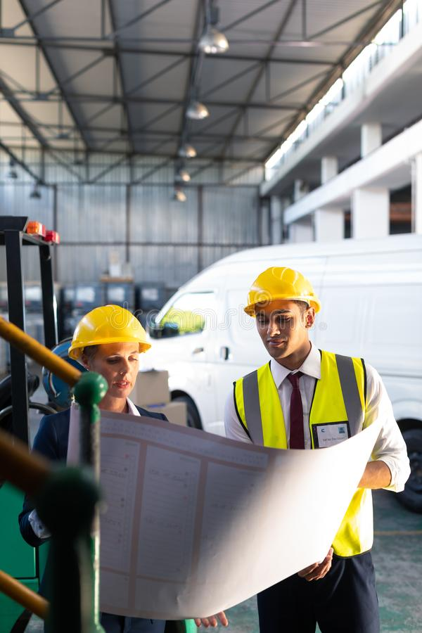 Female manager and male supervisor discussing over inventory chart in warehouse. Front view of Caucasian female manager and Caucasian male supervisor discussing stock photo