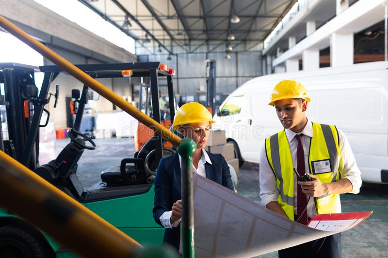 Female manager and male supervisor discussing over inventory chart in warehouse. Front view of Caucasian female manager and Caucasian male supervisor discussing stock photos