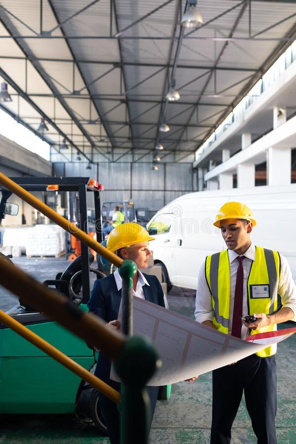 Female manager and male supervisor discussing over inventory chart in warehouse. Front view of Caucasian female manager and Caucasian male supervisor discussing royalty free stock photo