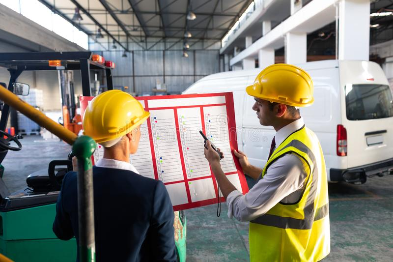 Female manager and male supervisor discussing over inventory chart in warehouse. Rear view of Caucasian female manager and Caucasian male supervisor discussing royalty free stock image
