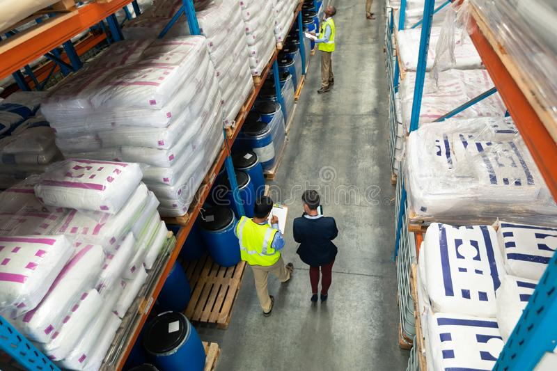 Female manager and male worker discussing over clipboard in warehouse stock images
