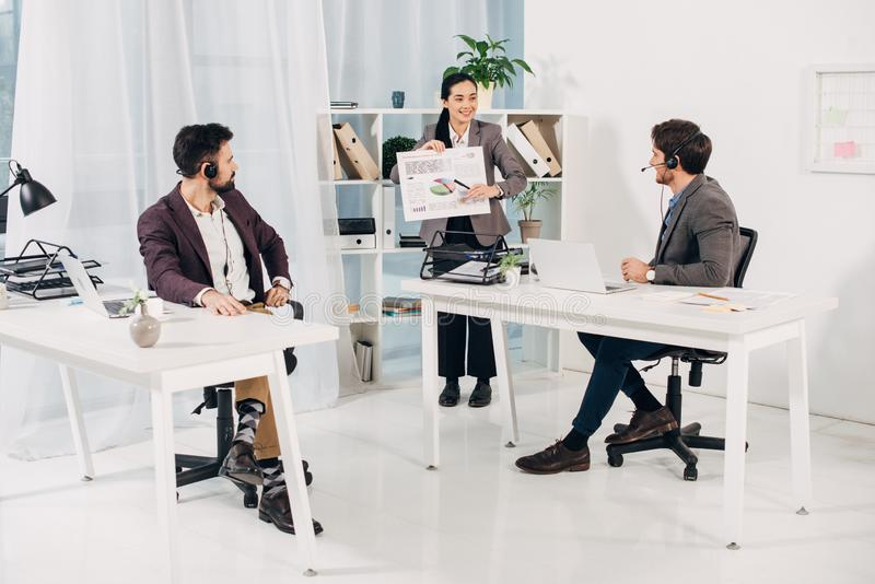 Female manager showing charts and graphs to male coworkers stock photos