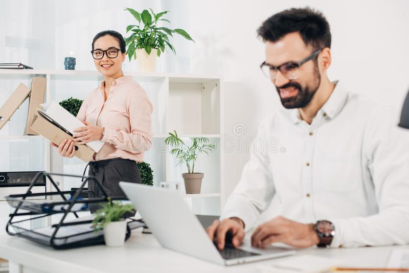 Female manager standing with folders while male coworker typing. At laptop keyboard royalty free stock image