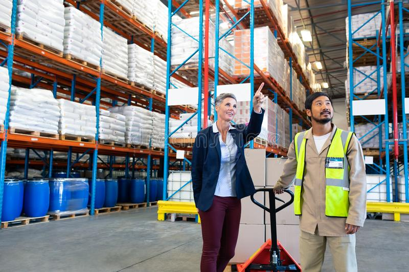 Female manager standing with worker and pointing at distance in warehouse stock image