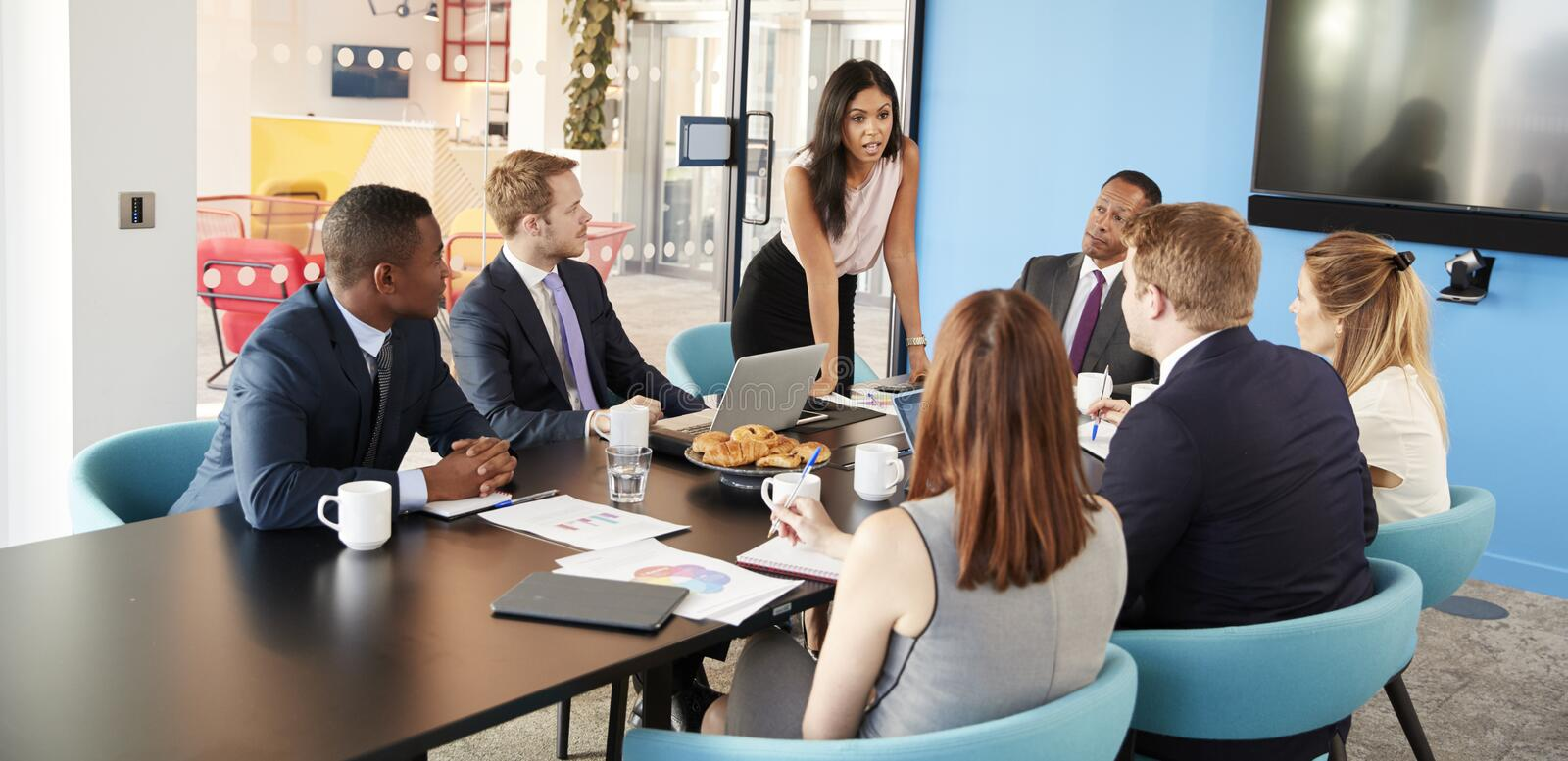 Female manager stands addressing colleagues in meeting room royalty free stock image