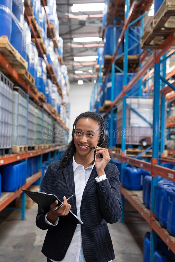 Female manager talking on headset while holding clipboard in warehouse. Happy female manager talking on headset while holding clipboard in warehouse. This is a stock photography