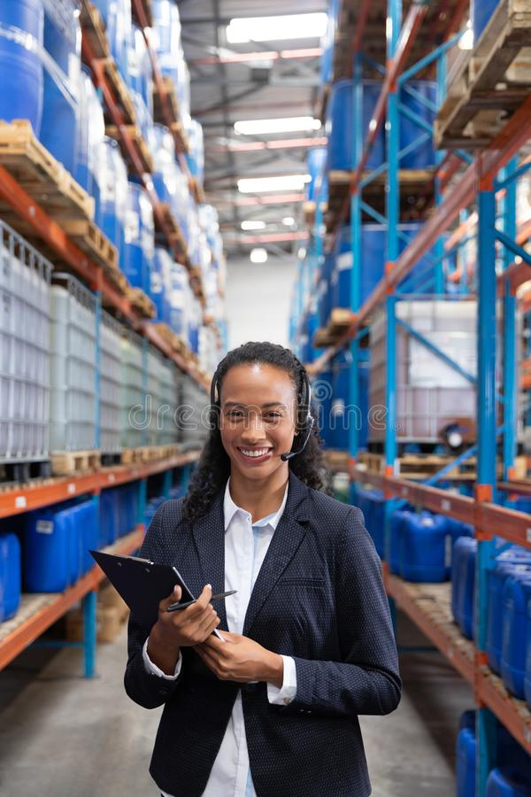 Female manager talking on headset while holding clipboard in warehouse. Portrait of female manager talking on headset while holding clipboard in warehouse. This stock photos