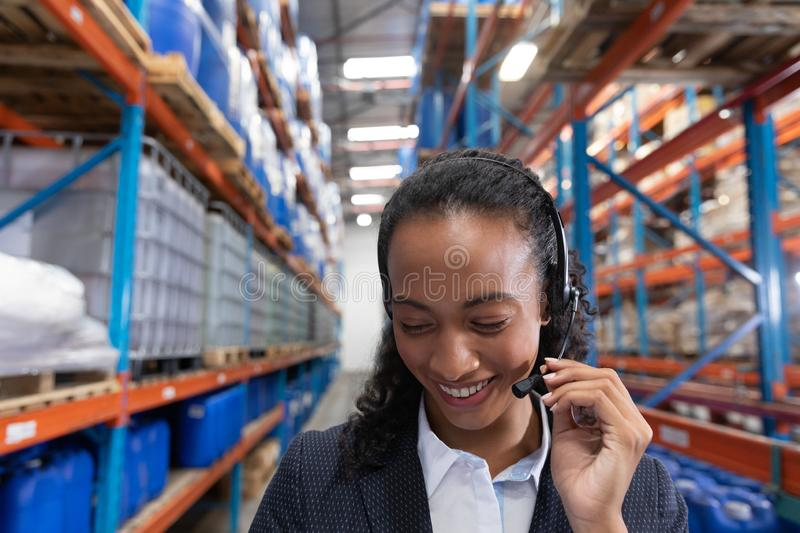 Female manager talking on headset in warehouse. Close-up of female manager talking on headset in warehouse. This is a freight transportation and distribution royalty free stock photos