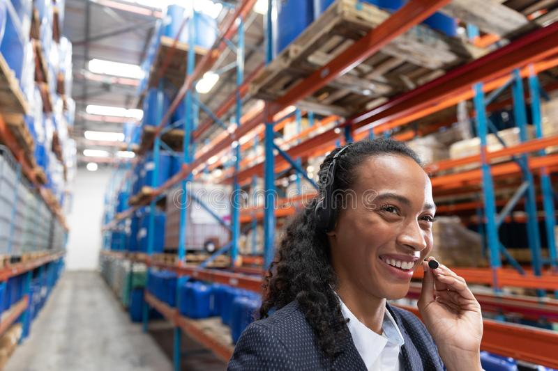 Female manager talking on headset in warehouse. Close-up of female manager talking on headset in warehouse. This is a freight transportation and distribution royalty free stock photo