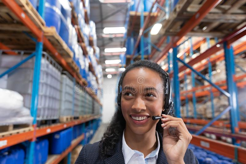 Female manager talking on headset in warehouse. Close-up of female manager talking on headset in warehouse. This is a freight transportation and distribution royalty free stock image