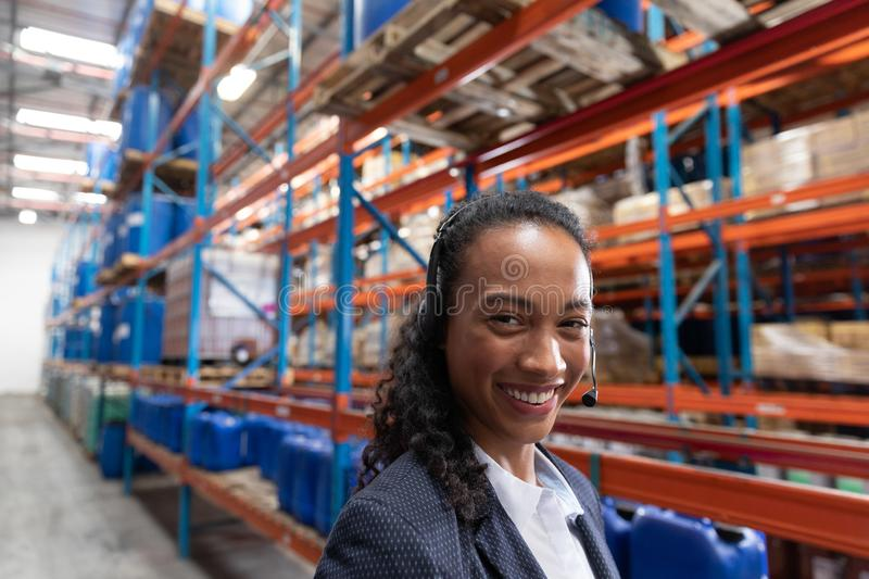 Female manager talking on headset in warehouse. Close-up of female manager talking on headset in warehouse. This is a freight transportation and distribution stock image