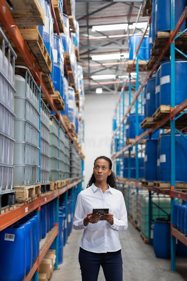 Female manager using digital tablet while checking stocks in warehouse. African American female manager using digital tablet while checking stocks in warehouse royalty free stock image