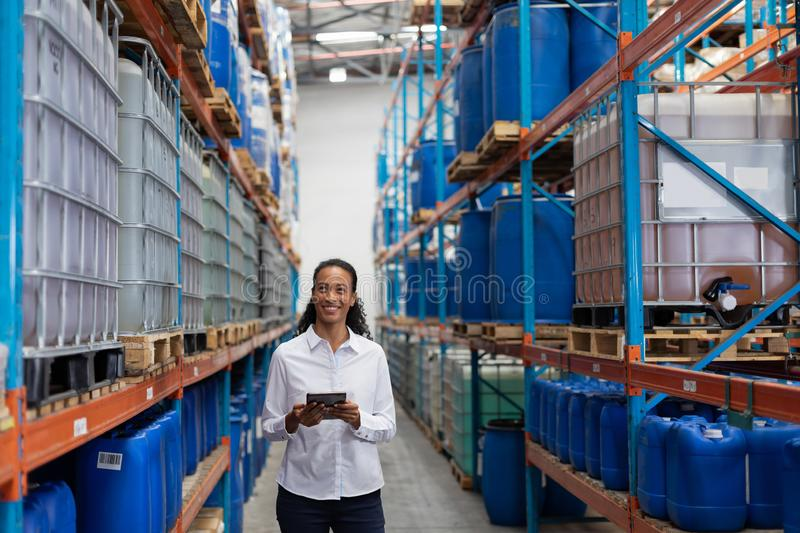 Female manager using digital tablet in warehouse. African American female manager using digital tablet in warehouse. This is a freight transportation and stock photos