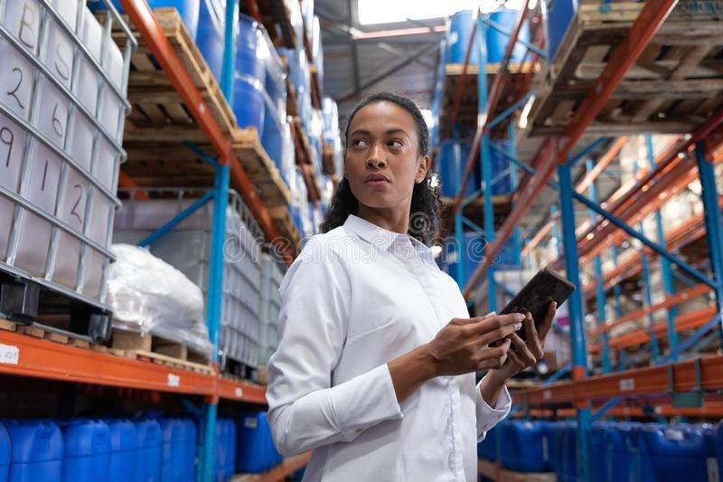 Female manager using digital tablet in warehouse. African American female manager using digital tablet in warehouse. This is a freight transportation and royalty free stock photos