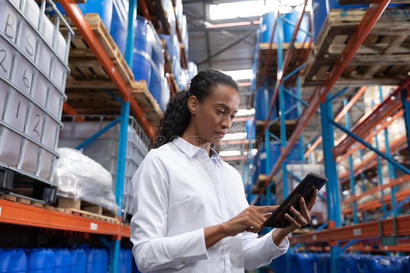 Female manager using digital tablet in warehouse. African American female manager using digital tablet in warehouse. This is a freight transportation and royalty free stock image