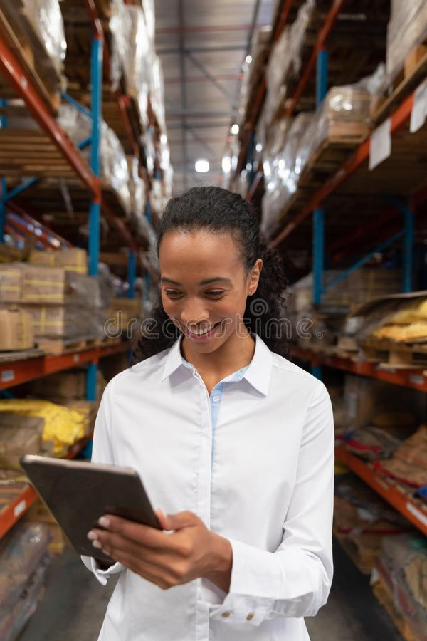 Female manager using digital tablet in warehouse. Happy female manager using digital tablet in warehouse. This is a freight transportation and distribution royalty free stock photos