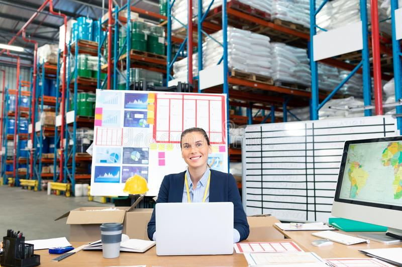 Female manager using laptop at desk in warehouse. Portrait of beautiful young Caucasian female manager using laptop at desk in warehouse. This is a freight royalty free stock images