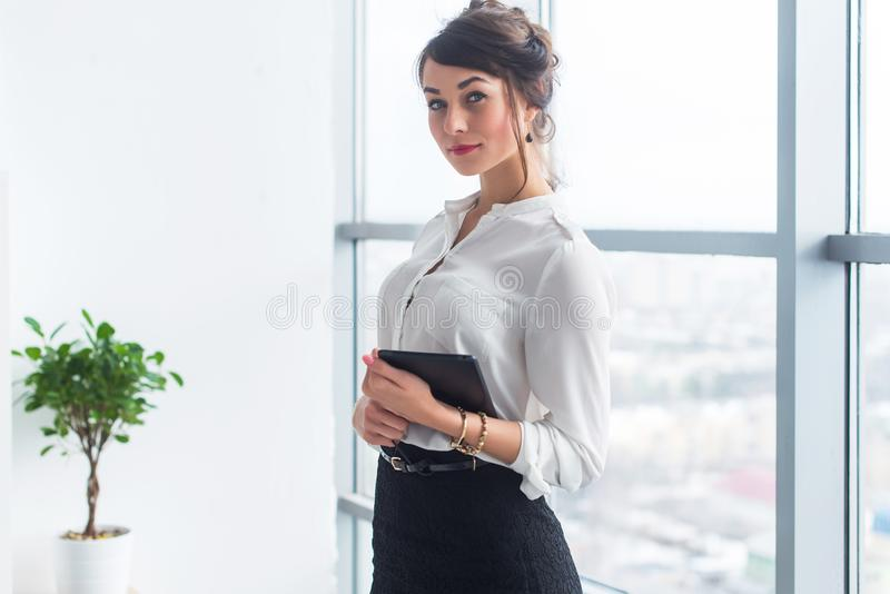 Female manager wearing office suit, standing, holding tablet in her hands, looking at camera. Female manager wearing office suit, standing, holding tablet in royalty free stock images